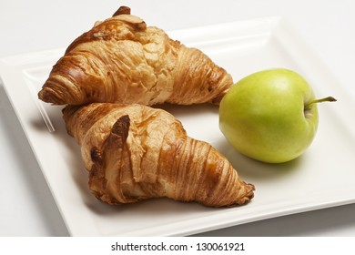 Two croissants and one apple on a white plate