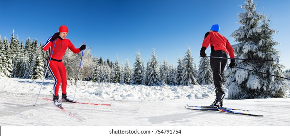 Two cross-country ski runners in front of wintry landscape