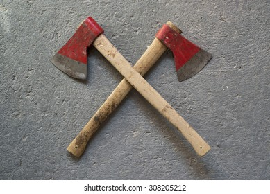 two crossed axes on a background of concrete