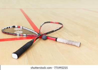 two crossed squash rackets and ball on the wooden floor. Racquetball equipment on the court on red lines. Photo with selective focus