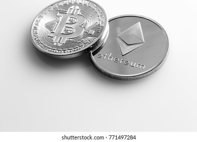 Two cryptocurrencies on a light surface.