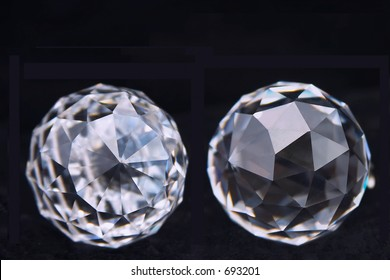 Two crystal globes with multi-faceted faces on black.
