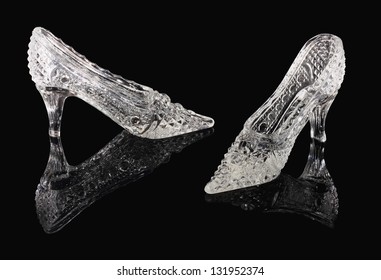 Two crystal shoes of the Cinderella stand on a black mirror