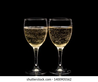 Two crystal wine glasses with a drink, falling ice and splashes