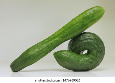 """Two cucumbers, one twisted and the other one straight, showing the concept """"Same but different""""."""