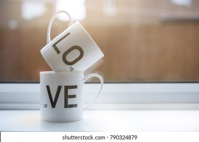 Two Cup of coffee with LOVE next to the window in retro tone, Stack of two white mug, Love concept ,Background for Valentine with copy space
