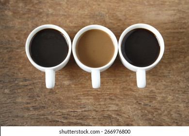 two cup of  hot black coffee, a cup of  instant coffee place on old wood background. three cup of coffee on old wood background.
