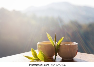 Two cup with tea leaf on table over mountains landscape with sunlight. Beauty nature background.