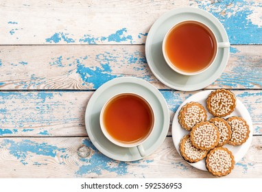 Two cup of tea and saucer with cookies on the table. Top view.