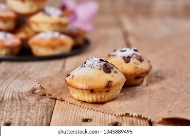 The two cupcakes with chocolate chips with powdered sugar lie on a kraft paper next to other cupcakes in a black baking sheet and orchid flower on a wooden background.