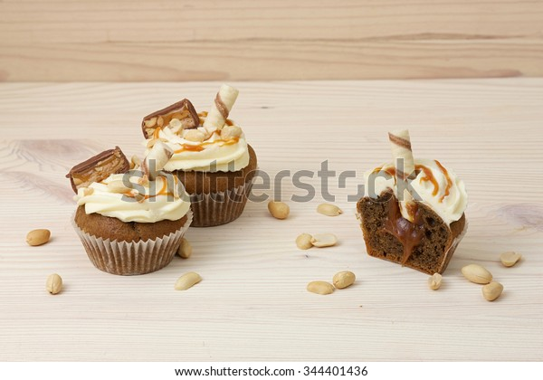Two cupcakes with salted caramel and half decorated cookies and peanuts on the wooden background