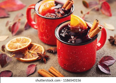 Two cups of autumn mulled wine or gluhwein with spices and orange slices on rustic table top view. Traditional drink on autumn holiday on the background of autumn leaves