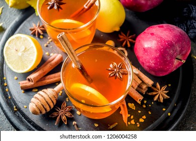 Two cups of autumn winter hot spicy tea with red apples, lemons, cinnamon, anise, honey, Dark rusty background copy space