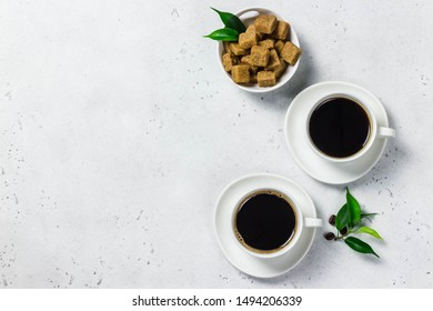 Two cups of black coffee, brown sugar. Top view, space for text.