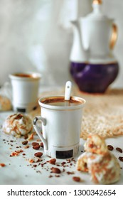 Two cups of black coffee, and ginger honey cookies on the table with coffee beans and kettle on the background. Vertical view, copy-space