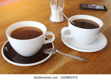 Two cups of black cofffee on wood table, morning coffee. Clouse-up.