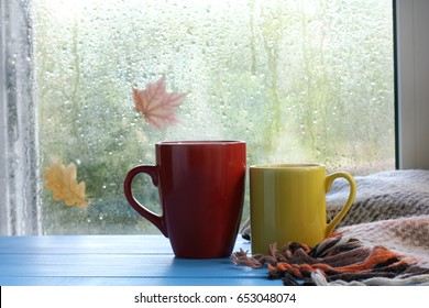 two cups and a blanket against the window with rain drops and leaves / warming the atmosphere in the rainy time