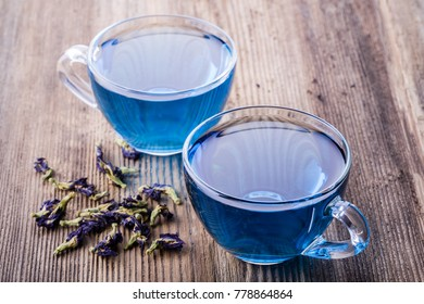 Two cups of Butterfly pea tea (pea flowers, blue pea) for healthy drinking, detox drinking on old wooden table