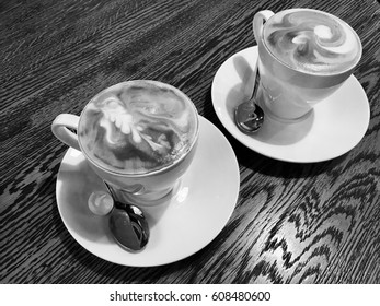 Two cups of cappuccino coffee stand on wooden table in the restaurant, black and white photo