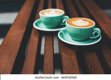 Two cups of cappuccino with latte art on wooden background. Beautiful foam, greenery ceramic cups, stylish toning, place for text.