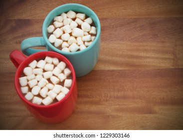 Two cups with cocoa drink and marshmallows on wooden table with room for text
