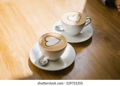 two cups of coffee with cream and chocolate syrup