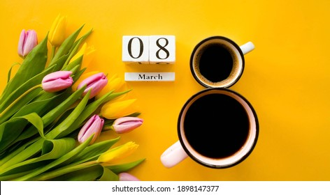 """Two cups of coffee, a delicate bouquet of tulips and numbers. Greeting card for Women's Day on March 8. Fashionable yellow background. March 8 and the concept of """"women's day""""."""