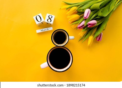 "Two cups of coffee, a delicate bouquet of tulips and numbers. Greeting card for Women's Day on March 8. Fashionable yellow background. March 8 and the concept of ""women's day""."