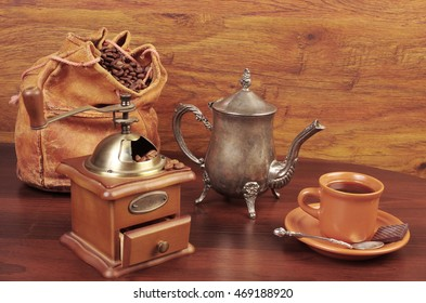Two cups of coffee, grinder, coffee pot.