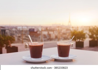 two cups of coffee or hot chocolate and Paris skyline at sunset, cafe with panoramic view of the city with Eiffel tower