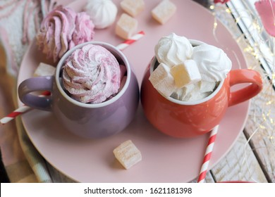 Two cups of coffee with meringues and marshmallows, Turkish delight on a plate, hearts, illumination, against the background of a window, homeliness, Valentine's day