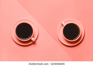 Two cups of coffee on minimal Two cups of coffee on minimalistic living coral color of the year 2019 background. background. Top view, flat lay. 16-1546