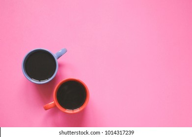 Two cups of coffee on a pink table in a coffee shop. The concept of dating, male and female. Flat lay minimalist photography