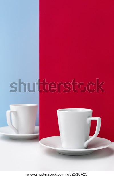 Two cups of coffee on red with a clean background for notes.