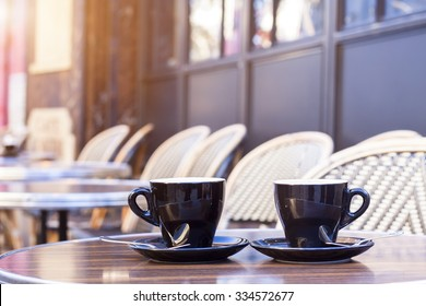 Two cups of coffee on restaurant terrace with afternoon sunlight