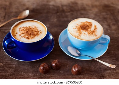 Two cups of coffee on a wooden table background