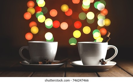 two cups of coffee on a wooden table on a background of colored lights