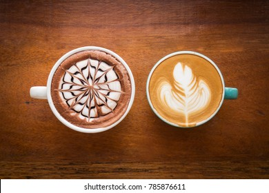 Two cups of coffee on wooden table. Latte art in flower or spider shape and leaf. Top view with dark vignette. Warm color tone.