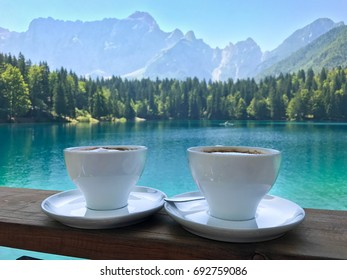 Two cups of coffee over the breathtaking view on alpine lake Fusine, Julian Alps, Italy