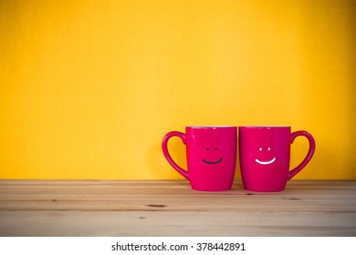 Two cups of coffee and stand together to be heart shape on yellow background with smile face on cup.