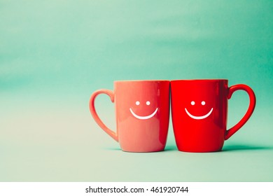 Two cups of coffee and stand together with smile face on cup.