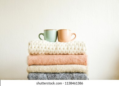 Two cups of coffee standing on bunch of knitted warm pastel color sweaters w/ different knitting patterns folded in stack. Fall winter knitwear clothing. Textured wall background. Close up, copy space