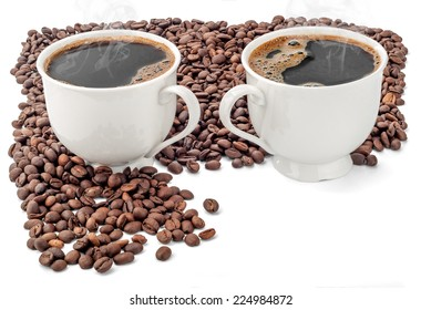 Two cups of coffee surrounded by coffee beans on white background. Extended Depth of Field and useful Copy Space in the lower right corner.