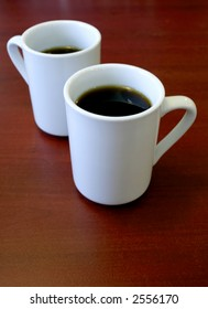 Two cups of coffee in white mugs on a wooden table.