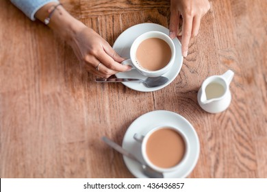 Two cups of coffee with woman hands on the wooden table in cafe background