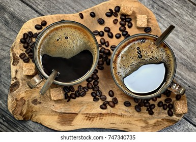 Two cups of coffee,coffee beans and brown lump sugar on wooden background.