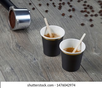 Two cups of espresso with chopsticks for blending on the background holder ground coffee. Environmentally friendly material.