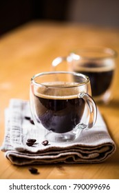 Two cups of espresso coffee on beige napkin in double botton glasses with butter cookie on wooden brown table background