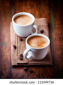 Two cups of espresso on rustic wooden table. Symbolic image. Coffee and coffee beans. Rustic wooden background. Close up.