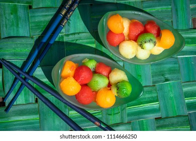 two cups filled with fruit balls of all colors on a green blue braided background